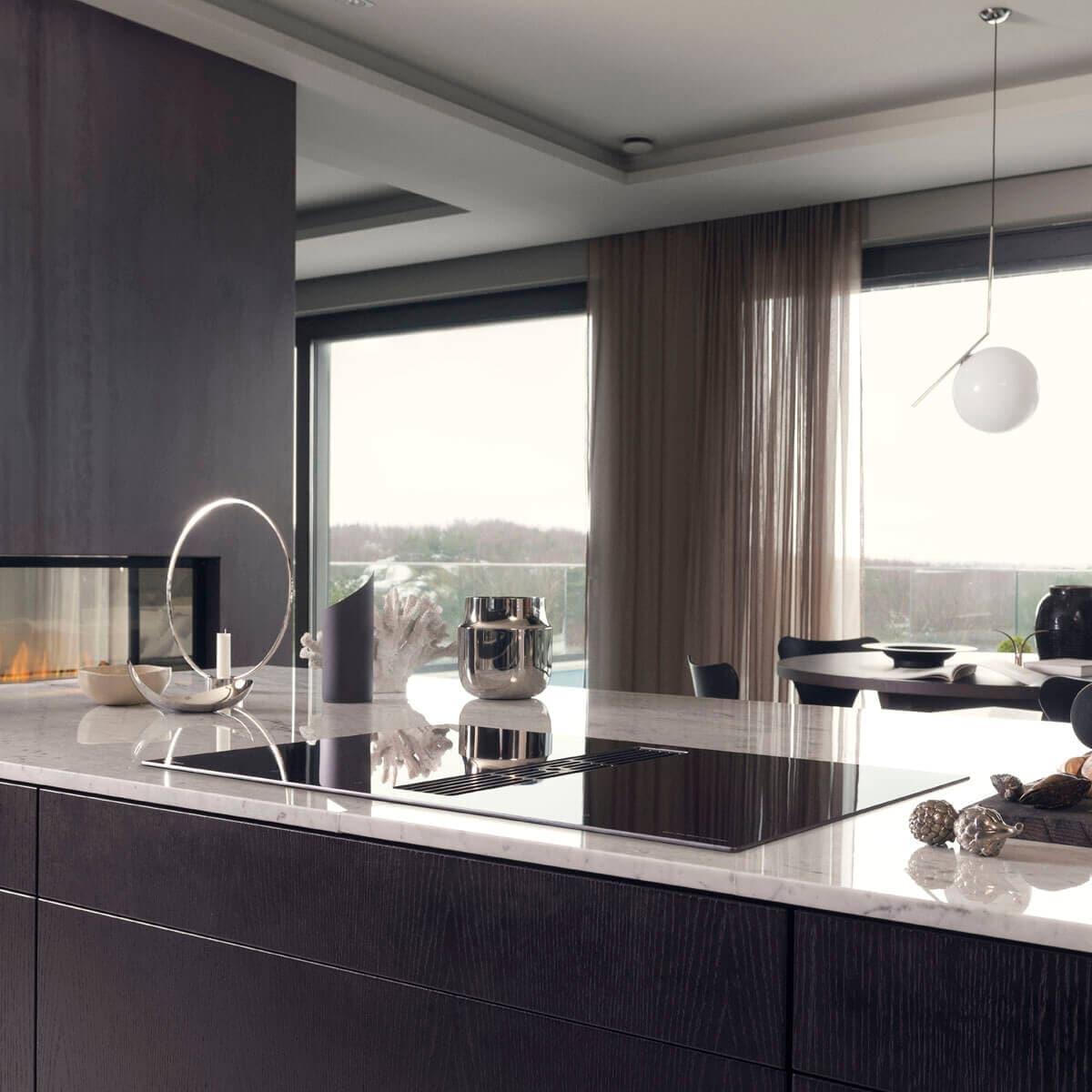 Bänkfläkten Vy som är inbyggd i induktionshäll monterad i modernt kök i mörka toner.