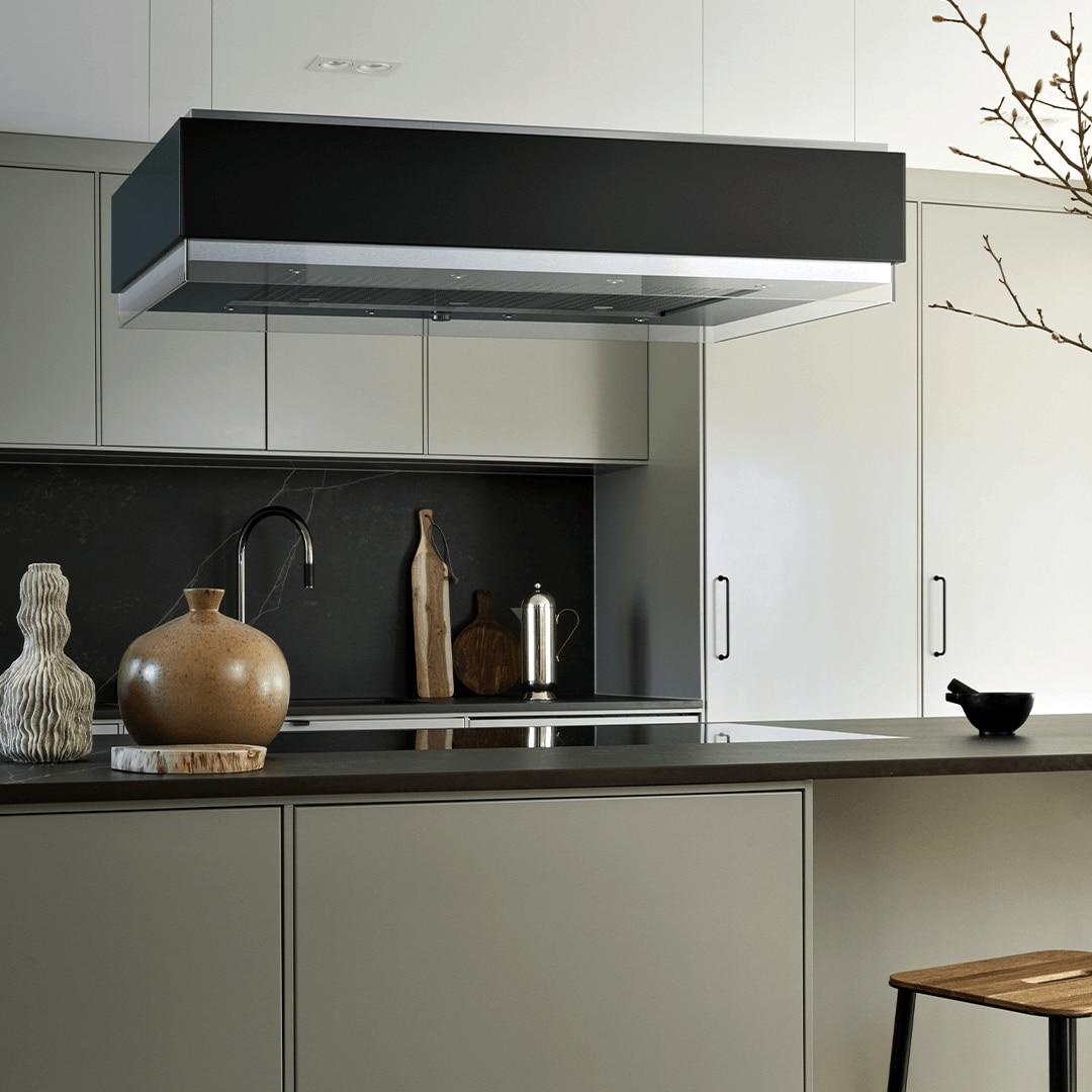 Frihängande köksfläkten Estrad i svart utförande ovanför köksö i traditionell köksmiljö.