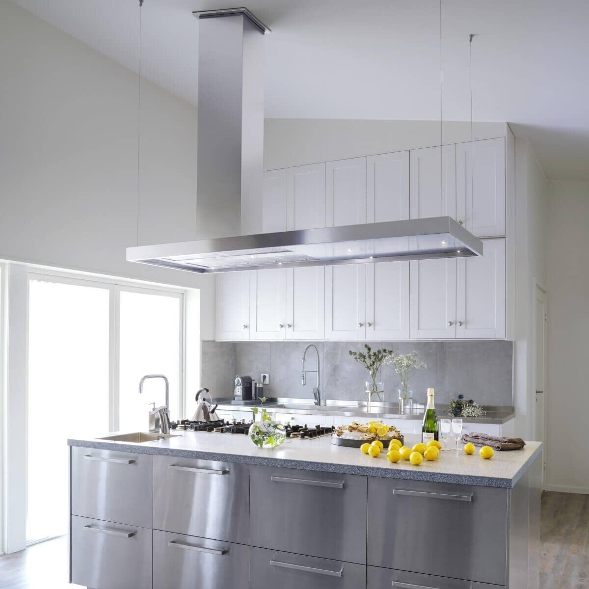 Frihängande köksfläkten Fokus i rostfritt i stort och öppet kök med lutande innertak.