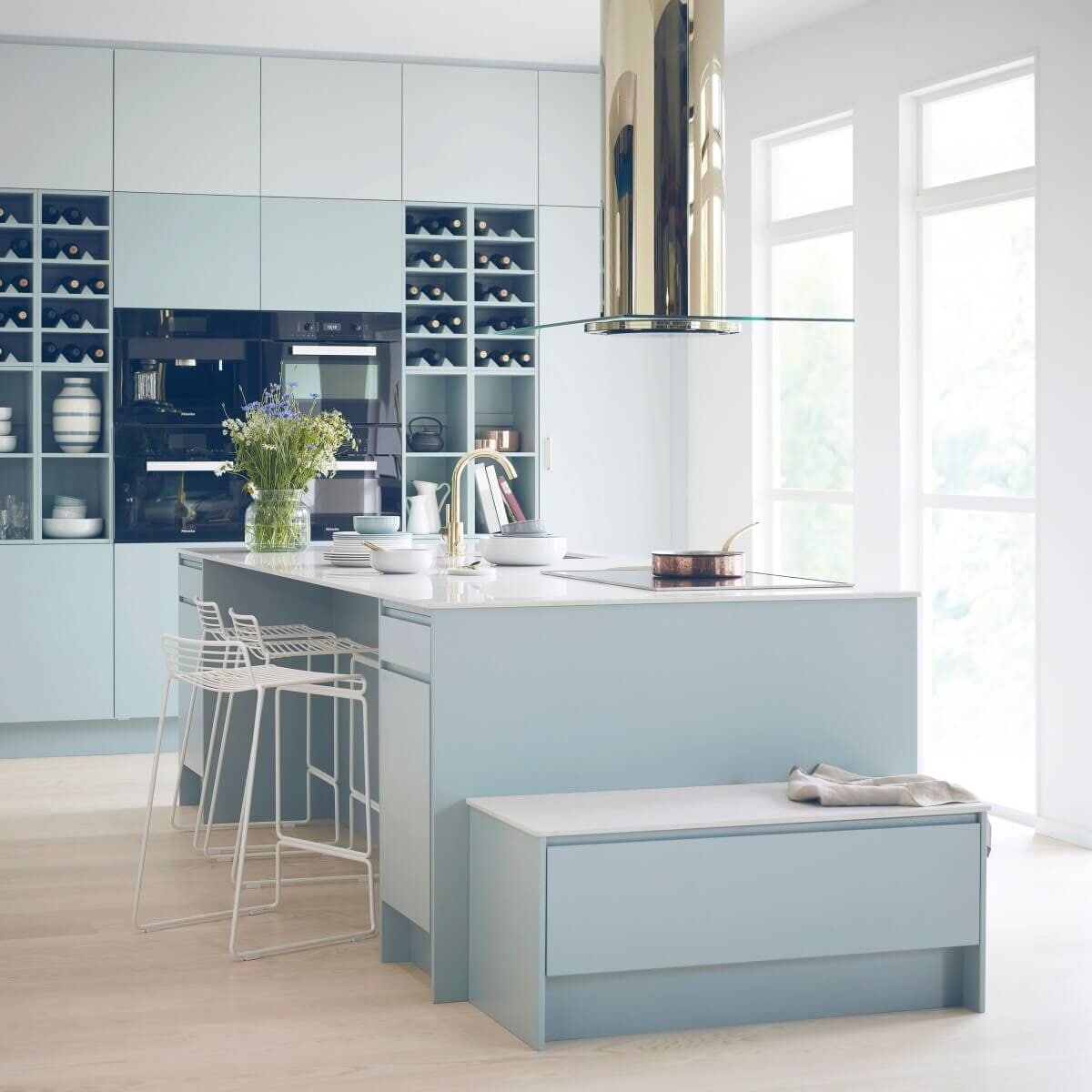 Frihängande köksfläkten Ikon i mässingutförande på avstånd i modernt kök i ljusblåa toner.