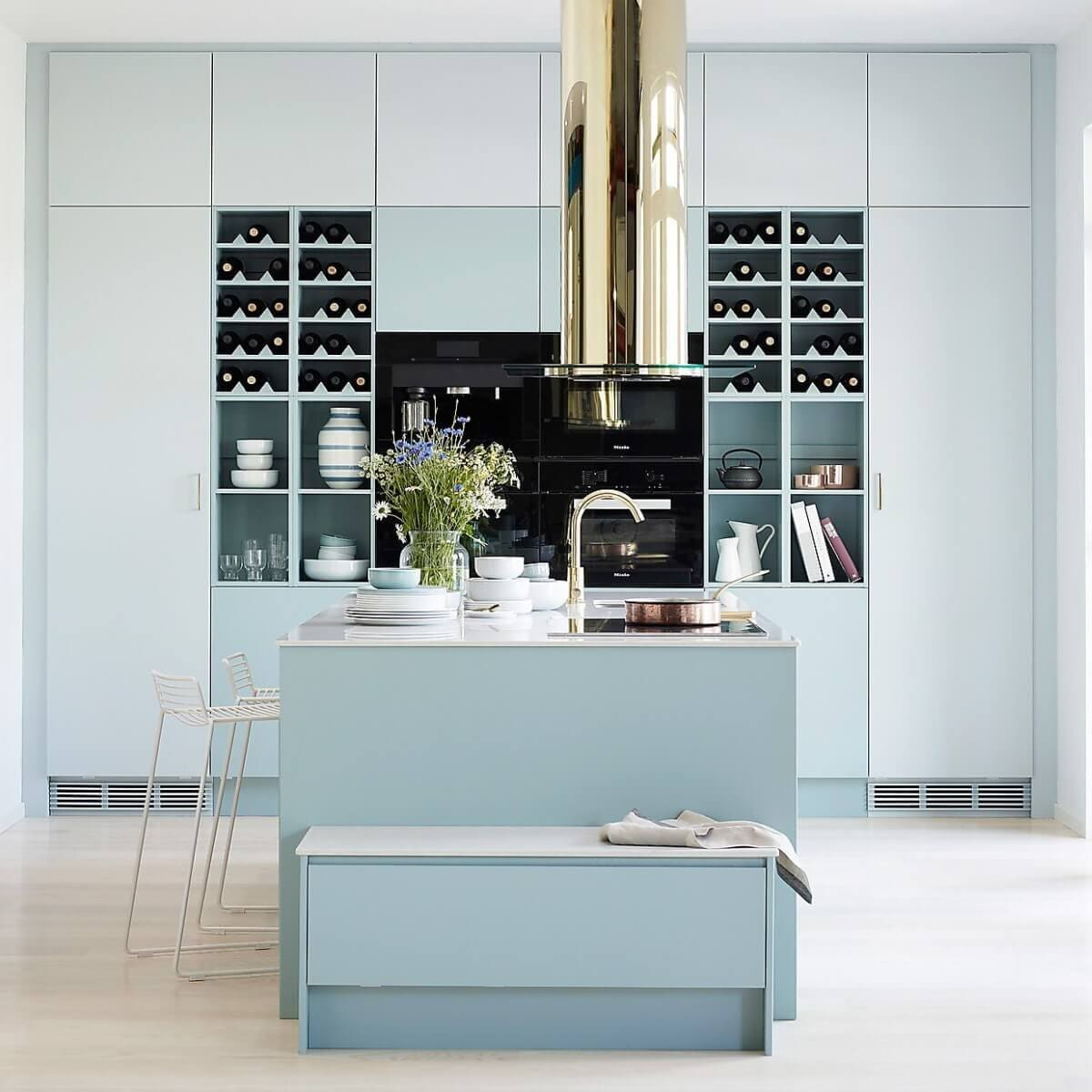 Frihängande köksfläkten Ikon i mässingutförande i modernt kök i ljusblåa toner.