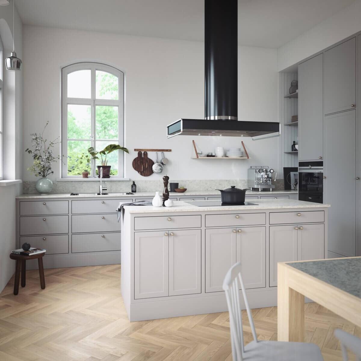 Frihängande köksfläkten Kafé i svart utförande skapar kontrast i ljus köksmiljö i sekelskiftesstil.