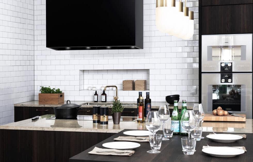 Frihängande köksfläkten Kub i svart utförande ovanför köksö i minimalistisk köksmiljö.