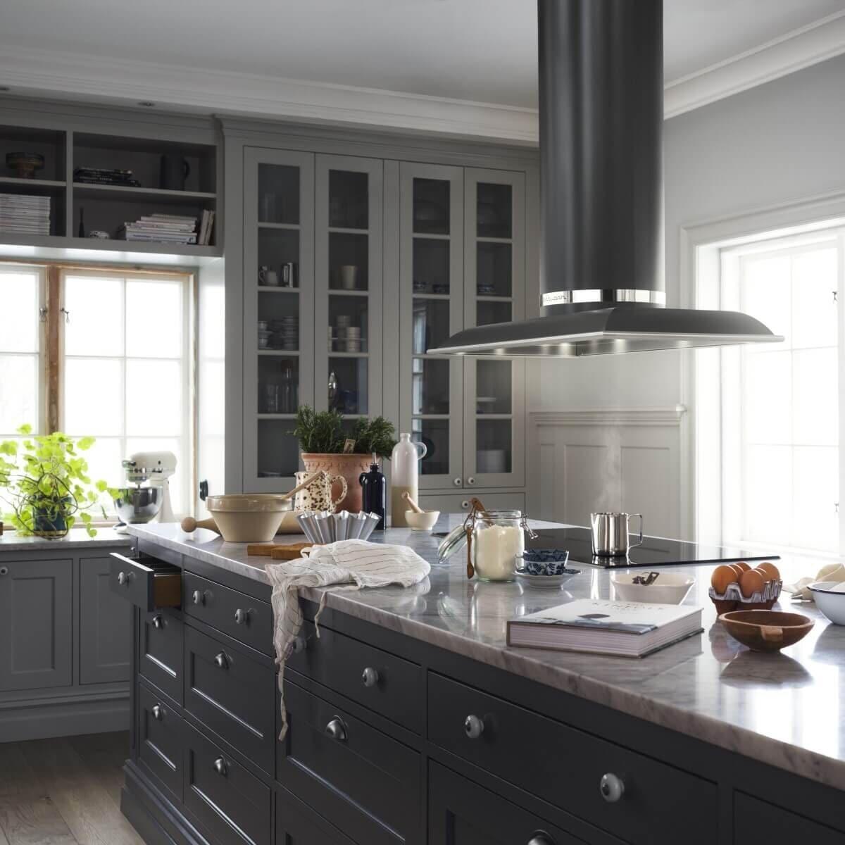 Frihängande köksfläkten Mixer i svart utförande ovanför köksö i lantlig köksmiljö med mörka köksluckor.