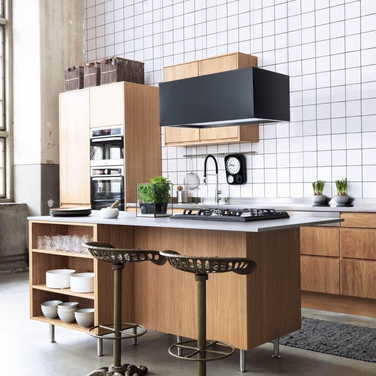 Frihängande köksfläkten Pendel i svart utförande ovanför ekfärgad köksö i minimalistisk köksmiljö.