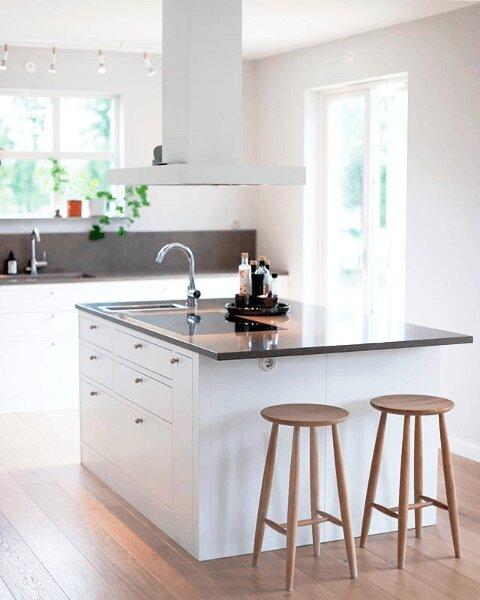 Frihängande köksfläkten Plan i vitt utförande ovanför köksmiljö i ljus traditionell stil.