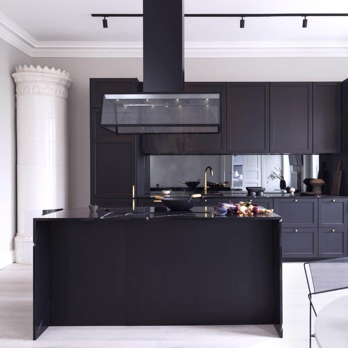 Frihängande köksfläkten Prisma i svart utförande ovanför köksö i modern sekelskiftesmiljö med mörka köksluckor.
