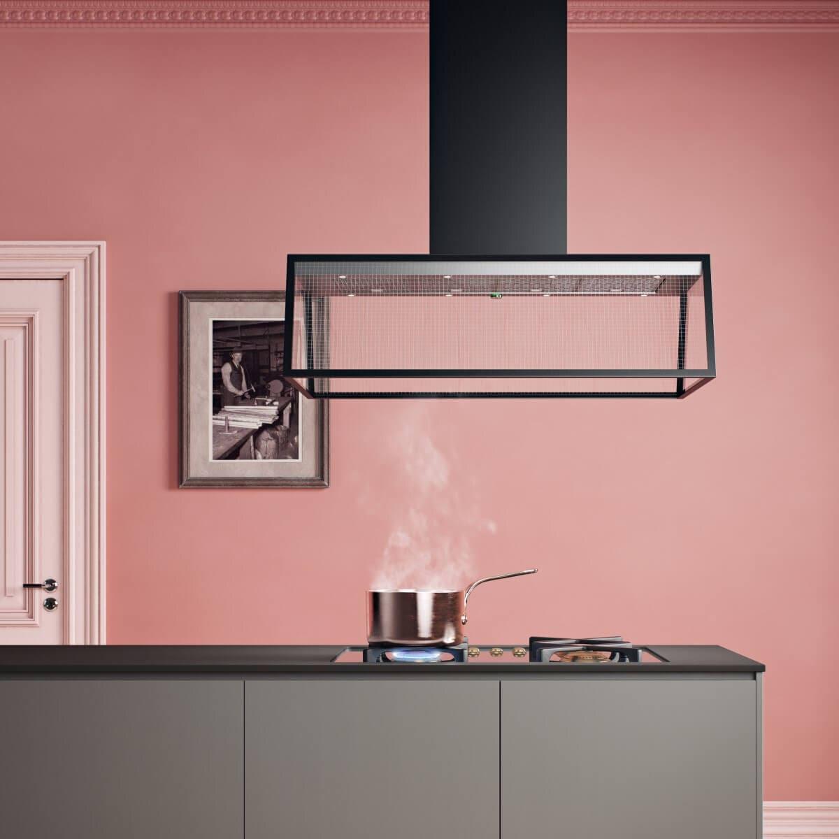 Frihängande köksfläkten Prisma i svart utförande ovanför köksö i minimalistisk kök med rosa toner.