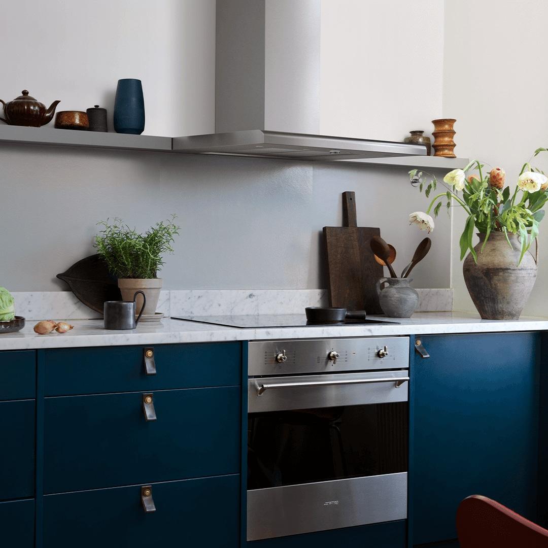 Vägghängda köksfläkten Intro i rostfritt utförande i minimalistisk köksmiljö med luckor som skapar kontrast.