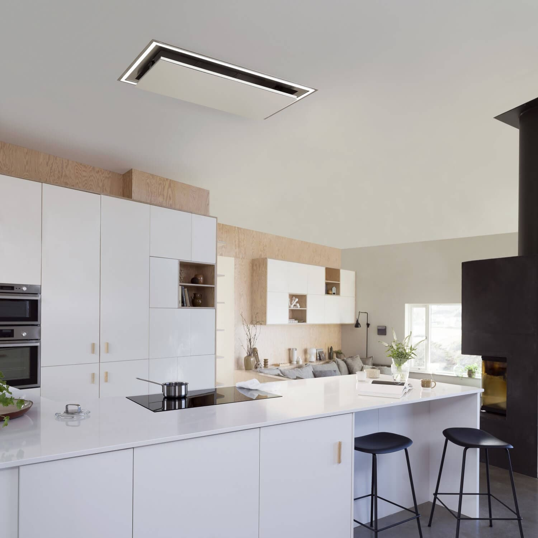 Takintegrerade köksfläkten Atrium i helvitt utförande med nedfälld lucka i ett ljust minimalistiskt kök.