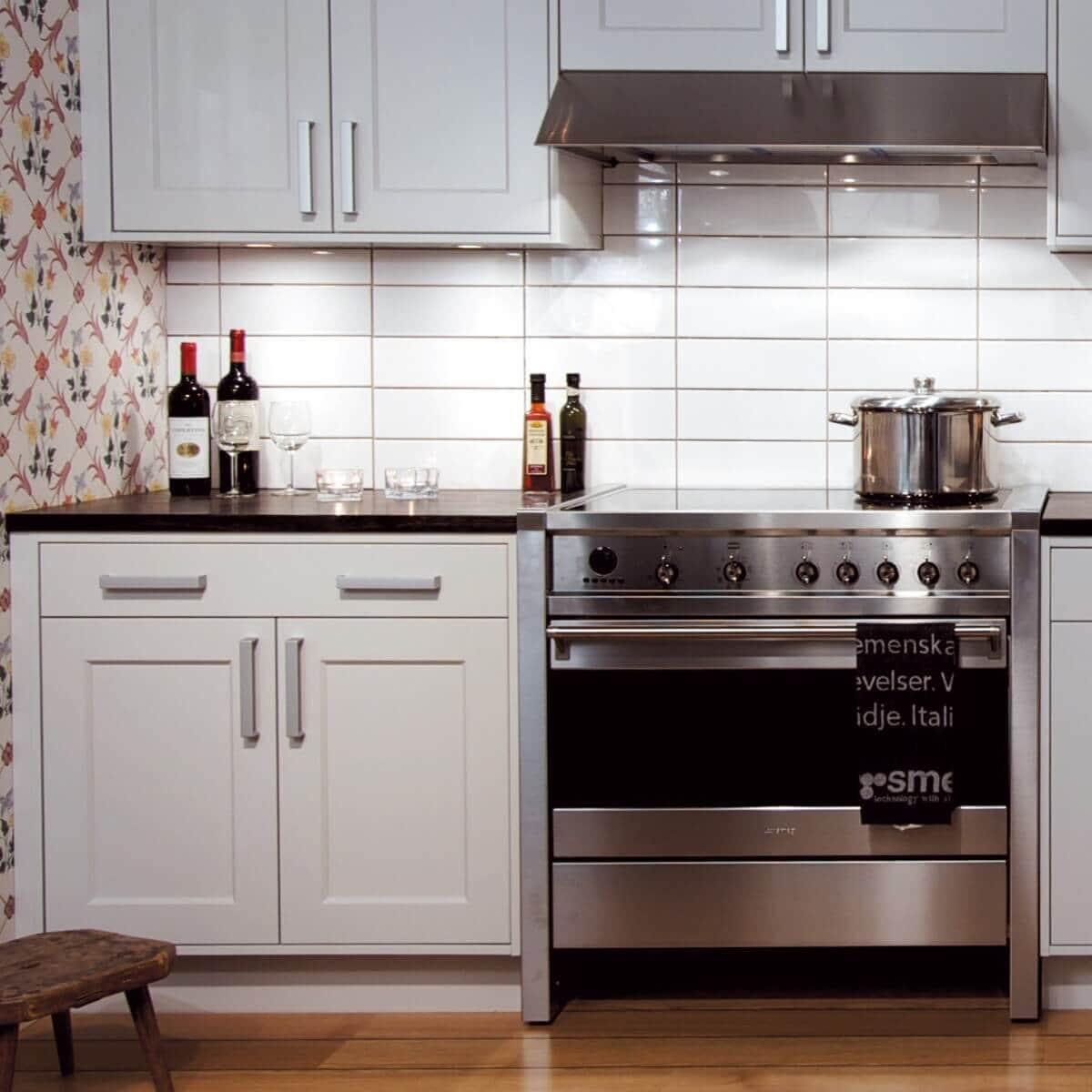 Underbyggnadsfläkten Accent i rostfritt utförande monterad under skåp ovanför rostfri spis i traditionell köksmiljö.
