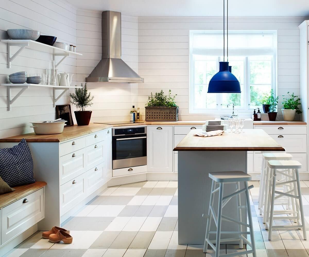 Vägghängda köksfläkten Exklusiv i rostfritt utförande i traditionell köksmiljö med ljus inredning.