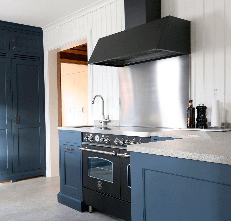 Vägghängda köksfläkten Aero i svart utförande skapar kontrast mot stänkskydd i rostfritt och ljust kakel i modernt kök med blåa köksluckor.