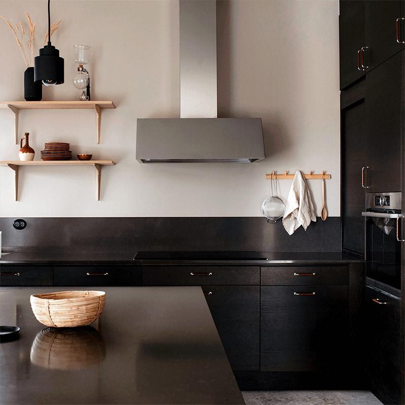 Vägghängda köksfläkten Aero i rostfritt utförande sticker ut i bland det minimalistiska kökets mörkare detaljer.