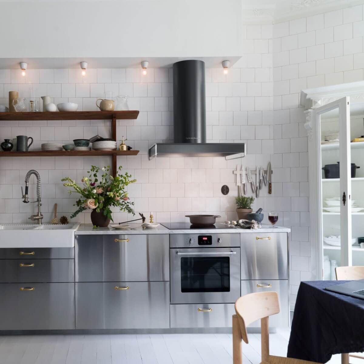 Vägghängda köksfläkten Bistro i svart utförande i ett industriellt köks vars rostfria luckor matchar med kåpans rostfria redskapsstänger.