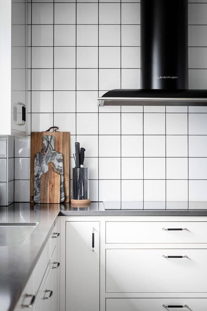 Vägghängda köksfläkten Blender i svart utförande i ett traditionellt kök där den står i kontrast mot ljus inredning.