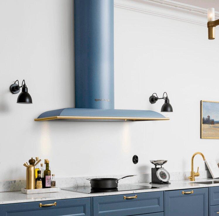 Vägghängda köksfläkten Blender i gråblått utförande med detaljer i mässing som matchar detaljerna i köksmiljön.