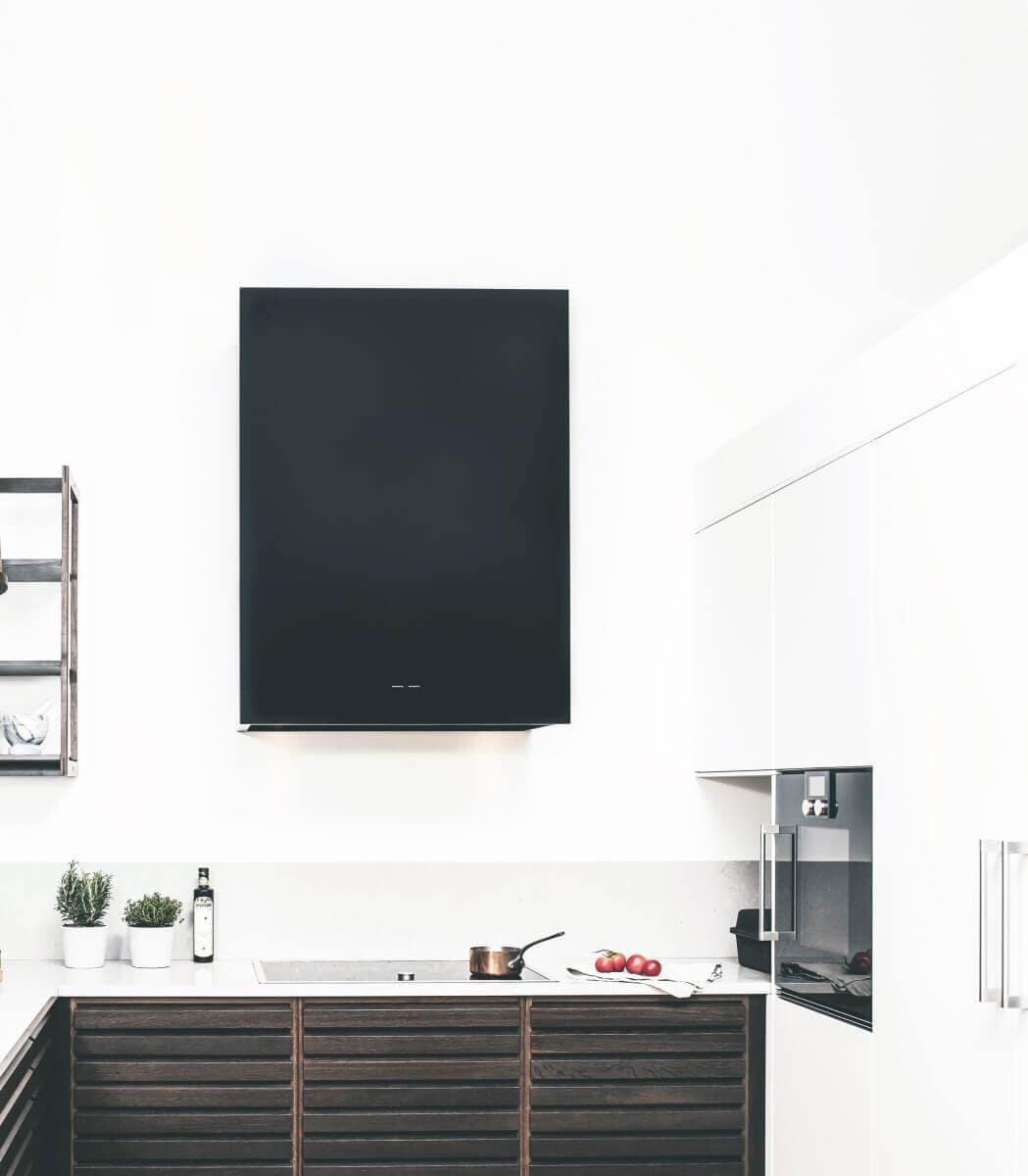 Vägghängda köksfläkten Box i svart utförande i en minimalistisk köksmiljö som skapar konstrast mellan vitt och svart.