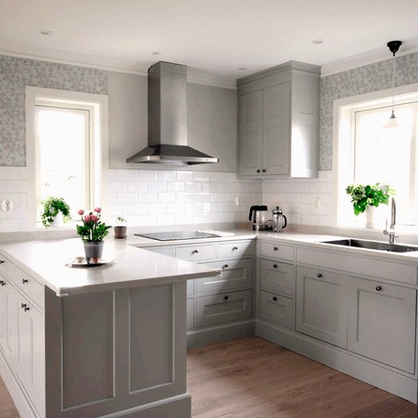 Vägghängda köksfläkten Carisma i rostfritt utförande i lantlig köksmiljö med vita marmorbänkar och ljusgråa köksluckor.