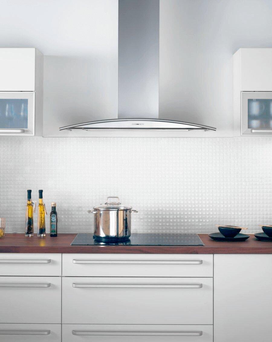 Vägghängda köksfläkten Cupol i rostfritt utförande i traditionell köksmiljö med vitt kakel.