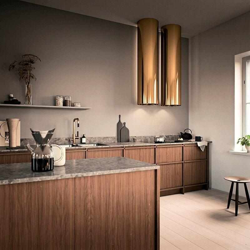 Två av den runda vägghängda köksfläkten Cylindra i mässingutförande  monterade bredvid varandra i modern köksmiljö.
