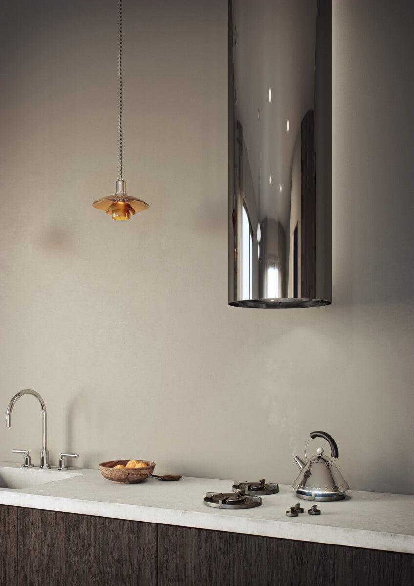 Runda vägghängda köksfläkten Cylindra i rostfritt utförande i minimalistisk köksmiljö.