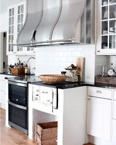 Vägghängda köksfläkten Era i rostfritt utförande i traditionell köksmiljö med vitrinskåp och vedeldad spis.