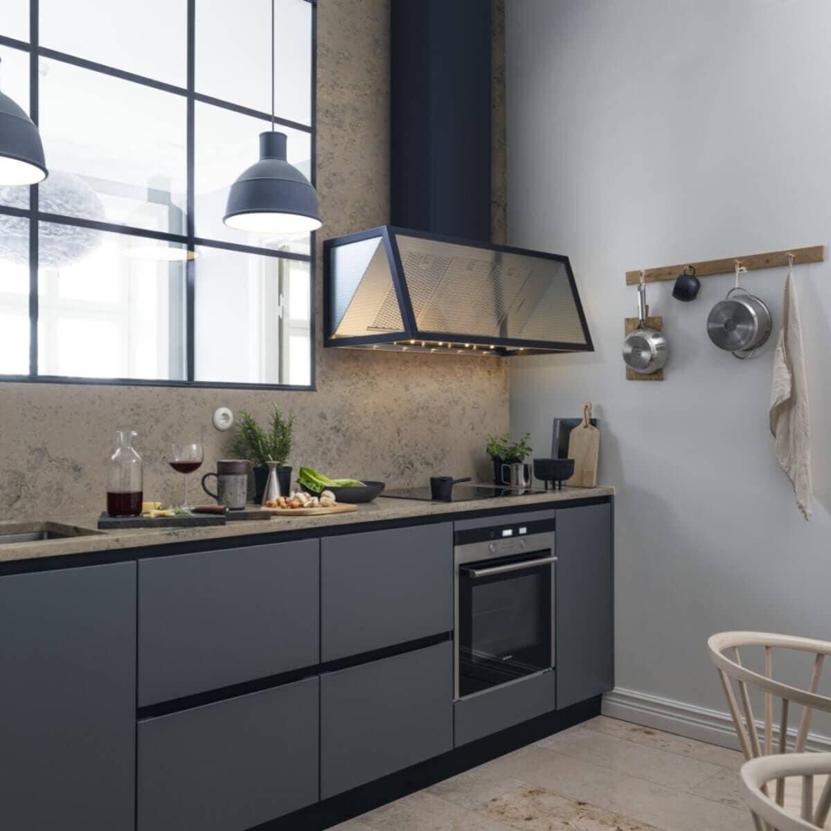 Vägghängda köksfläkten Fasett i svart utförande i modern köksmiljö med industrifönster och gråblåa köksluckor.