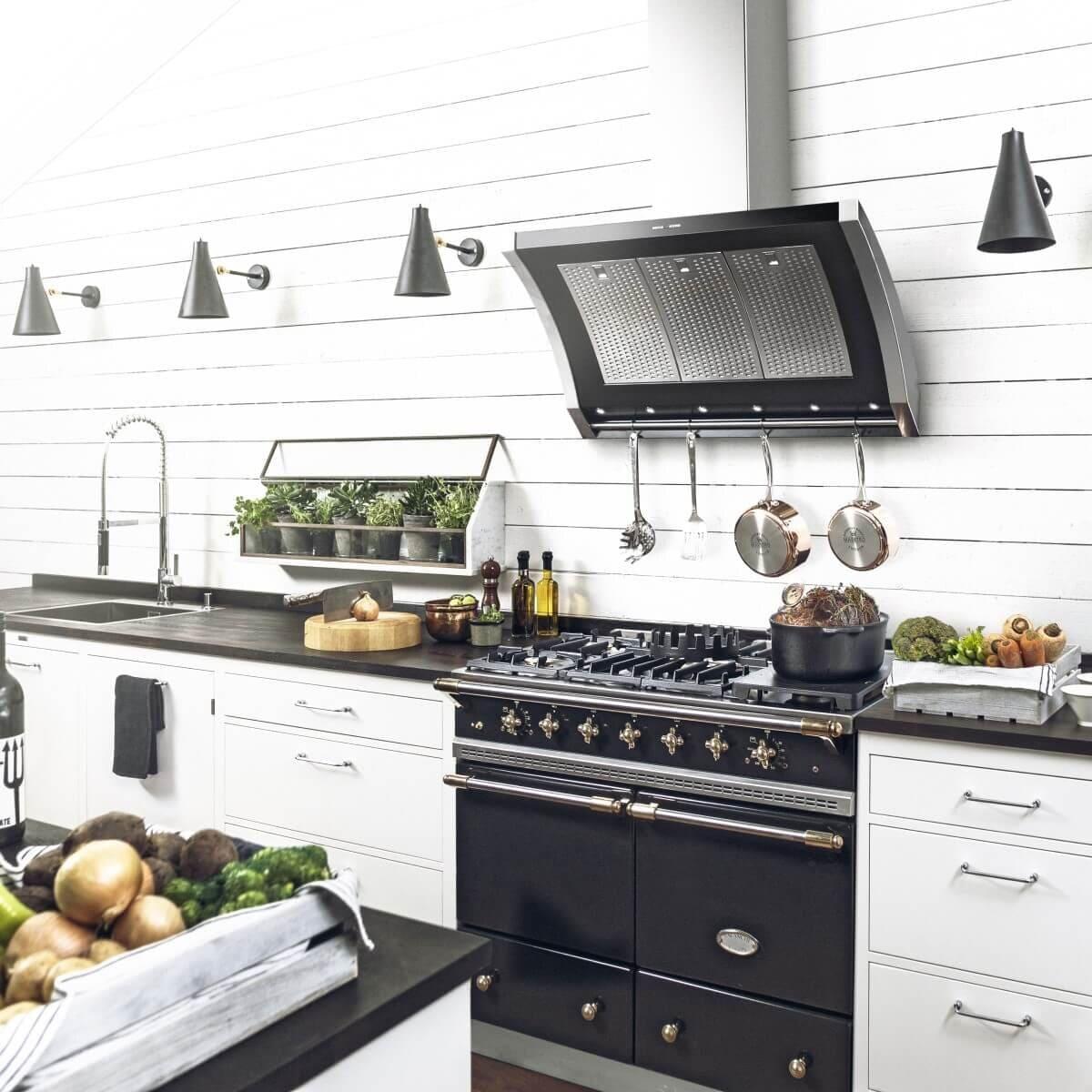 Vägghängda köksfläkten Rustik i svart utförande i lantlig köksmiljö med redskap i redskapsstång.