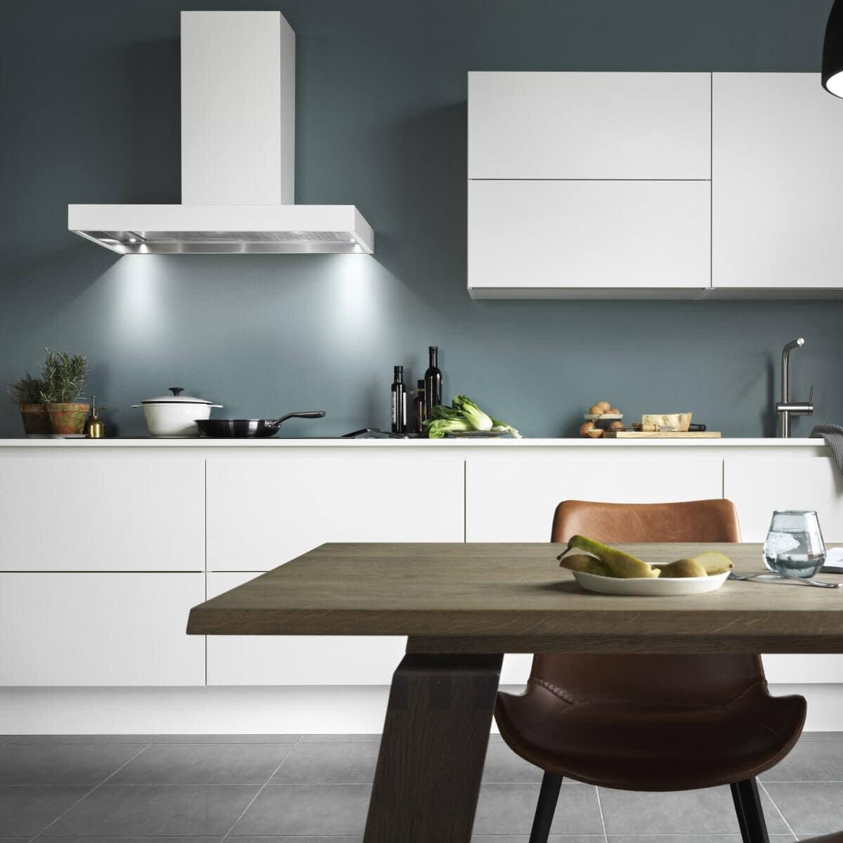 Vägghängda köksfläkten Strikt i vitt utförande i minimalist köksmiljö med vita köksluckor.